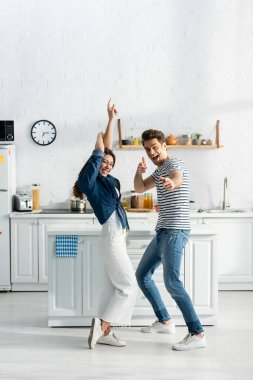 full length of excited couple dancing in modern kitchen