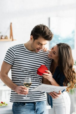 Happy man holding glass of wine and newspaper near cheerful girlfriend with heart-shaped gift box stock vector
