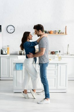 Full length of happy man embracing joyful girlfriend and smiling in kitchen stock vector