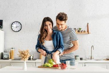 Joyful couple preparing salad in modern kitchen stock vector