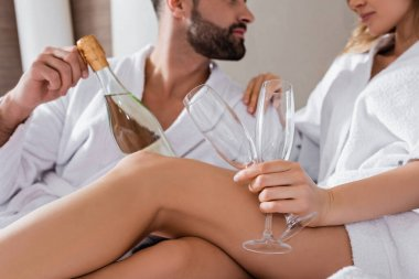 Cropped view of woman in white bathrobe holding champagne glasses near boyfriend with bottle on blurred background in hotel room stock vector
