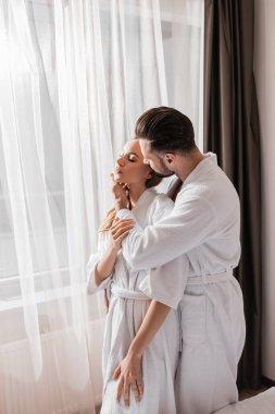 Man in bathrobe touching face of girlfriend near window in hotel stock vector