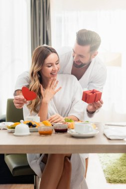 Smiling man holding present and paper heart near girlfriend in bathrobe and breakfast on blurred foreground in hotel stock vector