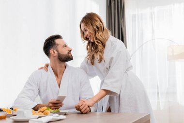 Smiling woman in bathrobe looking at boyfriend with smartphone near breakfast on blurred foreground in hotel stock vector