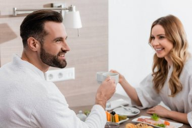 Smiling man in bathrobe holding cup near breakfast and girlfriend on blurred background in hotel stock vector