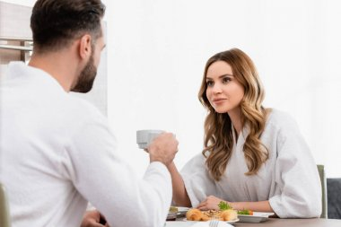 Woman in bathrobe holding cup and looking at boyfriend near breakfast on blurred foreground in hotel stock vector