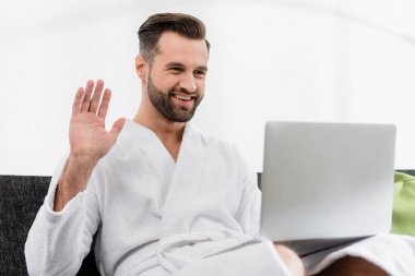 Cheerful man in bathrobe having video call on laptop on blurred foreground in hotel room stock vector
