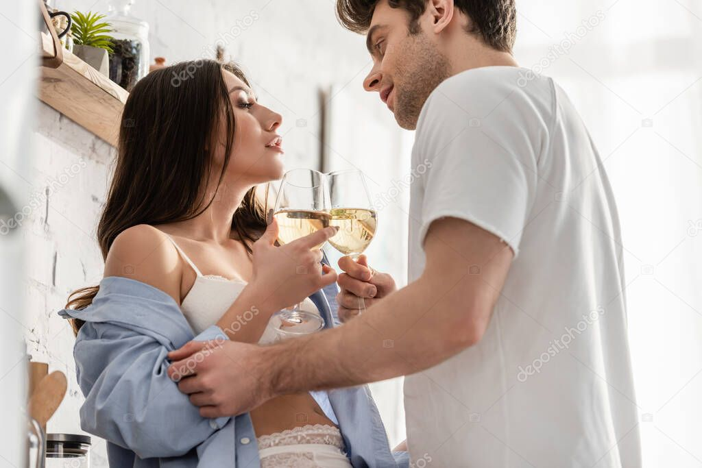 Side view of sexy couple holding glasses with wine and looking at each other stock vector