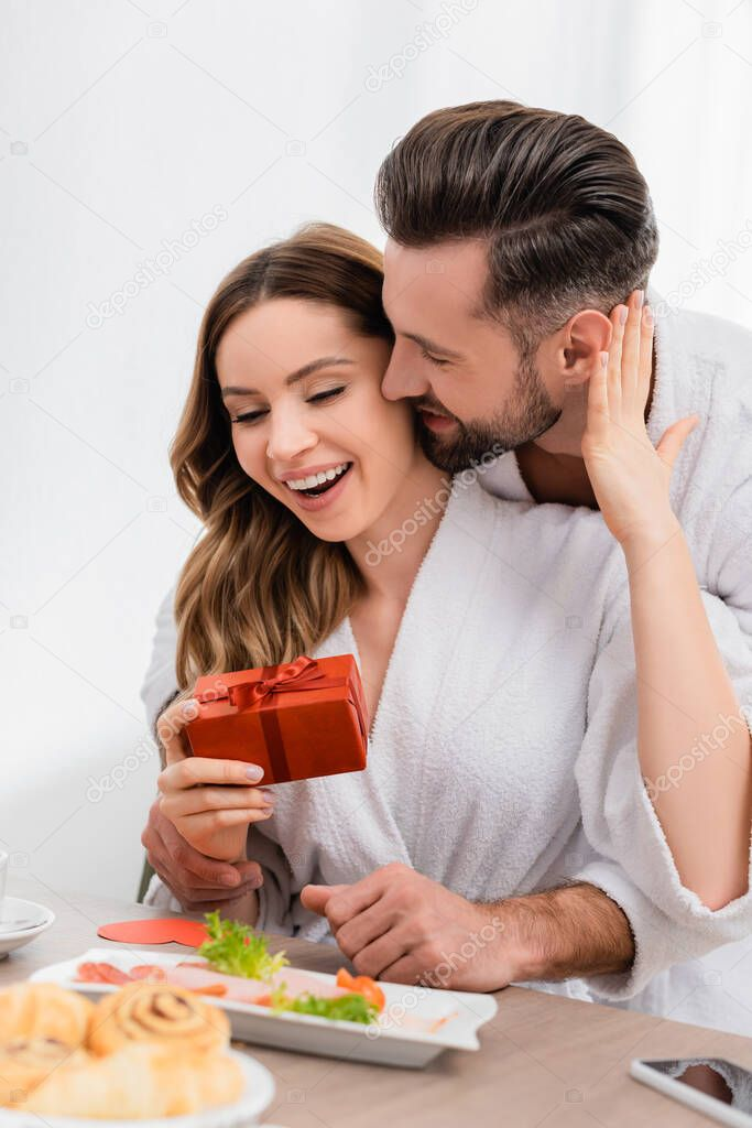 Cheerful woman in bathrobe touching boyfriend while holding gift box near breakfast on blurred foreground in hotel stock vector