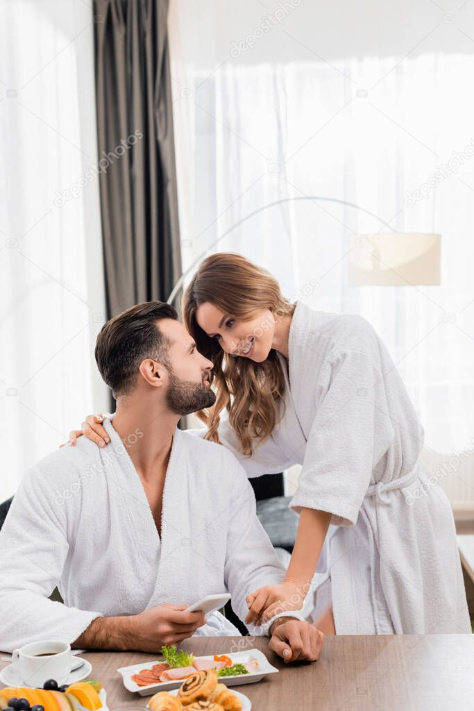 Smiling woman hugging boyfriend in bathrobe with smartphone near breakfast and coffee on blurred foreground in hotel room stock vector