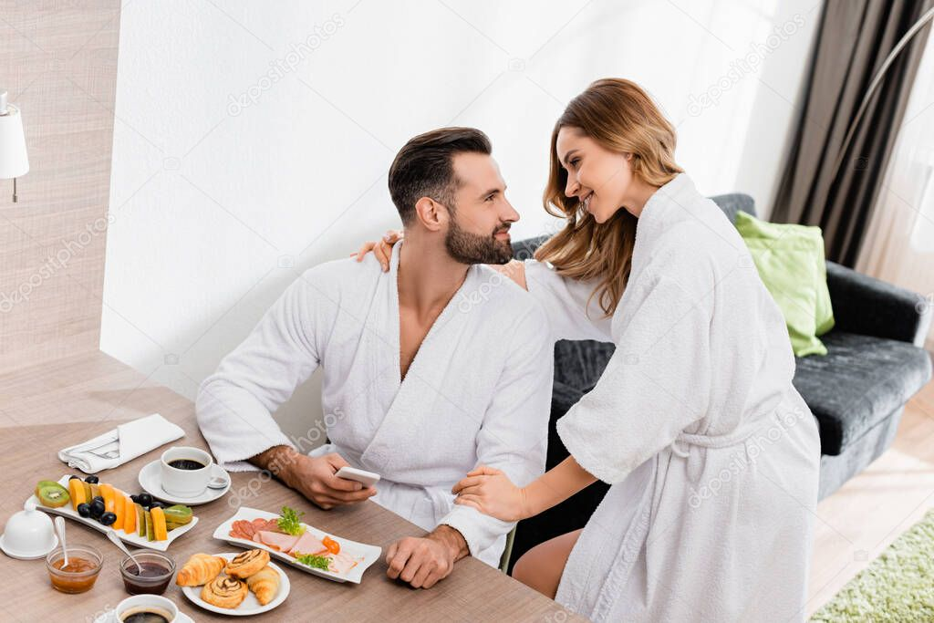 Woman in bathrobe embracing boyfriend with smartphone near delicious breakfast and coffee in hotel room stock vector
