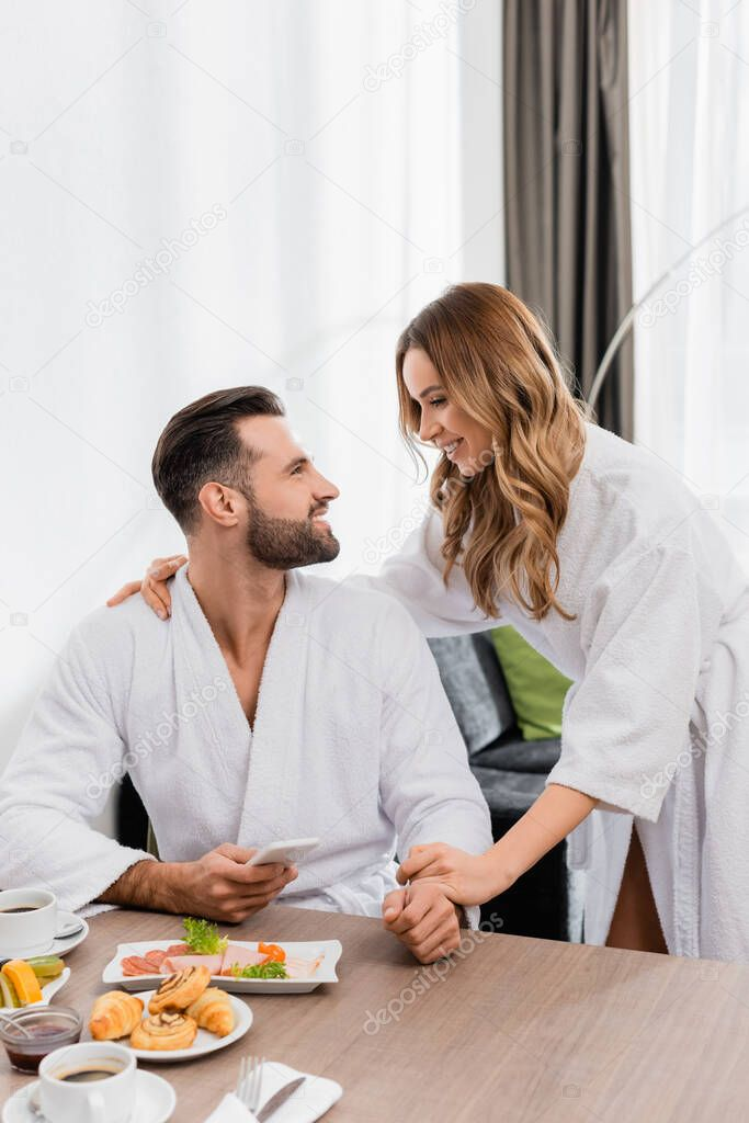 Smiling man with smartphone looking at girlfriend in bathrobe near breakfast with coffee on blurred foreground in hotel stock vector