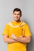 Veselý student ve žlutém oblečení drží notebook na šedém pozadí