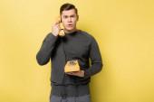 Muž v šedém svetru mluví na retro telefon na žlutém pozadí