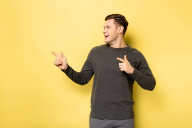 Smiling man pointing with fingers on yellow background stock vector