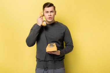 Man in grey pullover talking on vintage telephone on yellow background stock vector