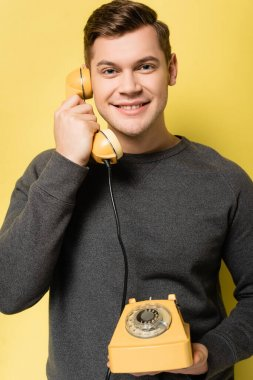 Smiling man looking at camera while talking on vintage telephone on yellow background stock vector