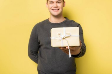Gift box in hand of smiling man blurred on yellow background stock vector