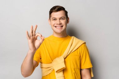 Smiling man in yellow clothes showing ok gesture on grey background stock vector