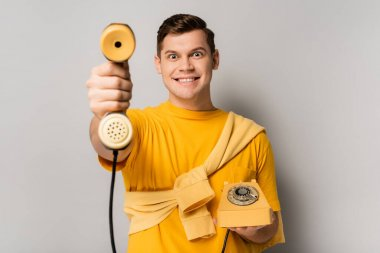 Cheerful man holding telephone handset on blurred foreground on grey background stock vector