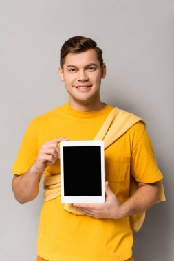 Young man in yellow t-shirt smiling while holding digital tablet with blank screen on grey background stock vector