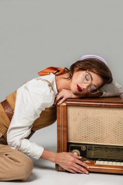 pretty stylish woman leaning on vintage radio receiver while listening music with closed eyes on grey