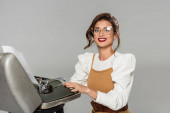 cheerful secretary typing on retro typewriter and smiling at camera isolated on grey