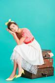 nachdenkliche Pin-up-Frau hält die Hände vor dem Gesicht, während sie auf Vintage-Koffern auf Türkis sitzt