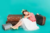 mosolygós pin up nő nézi kamera közelében vintage bőröndök és írógéppel abban az esetben, türkiz