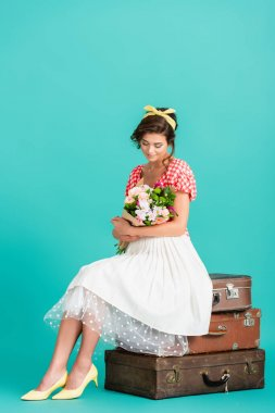 Young woman in retro clothes sitting on vintage suitcases with bouquet on turquoise stock vector