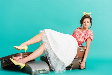 Young pin up woman sitting on vintage suitcases on turquoise stock vector