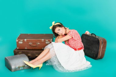 Smiling pin up woman looking at camera near vintage suitcases and typewriter in case on turquoise stock vector