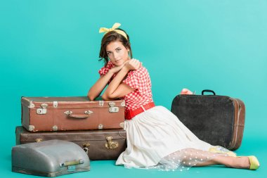 Smiling pin up woman looking at camera near suitcases and typewriter in case on turquoise stock vector