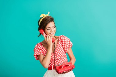 Happy pin up woman talking on retro phone isolated on turquoise stock vector