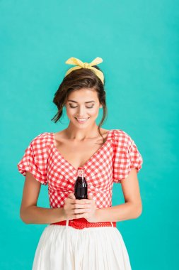Happy young woman in retro clothes holding bottle of soda isolated on turquoise stock vector