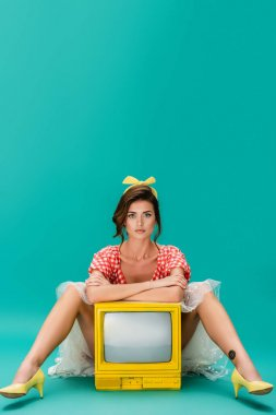 Pin up woman looking at camera while leaning with crossed arms on yellow vintage tv on turquoise stock vector