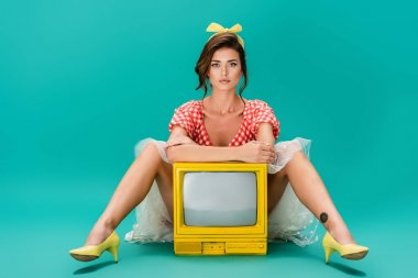 Young pin up woman looking at camera while sitting near bright yellow vintage tv on turquoise stock vector