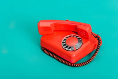 Bright red vintage landline phone on turquoise background stock vector