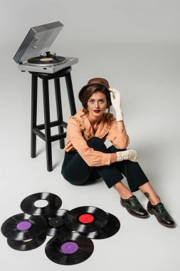 high angle view of stylish woman touching hat while sitting near vinyl discs and record player on grey