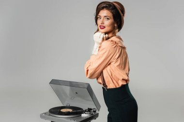 stylish woman with hands near face looking at camera near record player isolated on grey