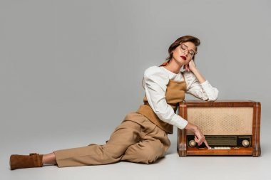 pretty trendy woman pressing button on vintage radio receiver while listening music on grey