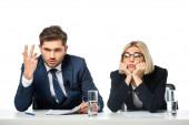 znechucený televizní přijímač gestikulující poblíž rozrušeného kolegy na pracovišti izolovaném na bílém
