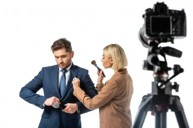 Blonde makeup artist with cosmetic brush near news anchor buttoning his blazer isolated on white, blurred foreground stock vector