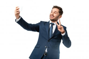 Cheerful businessman showing victory gesture while taking selfie isolated on white stock vector