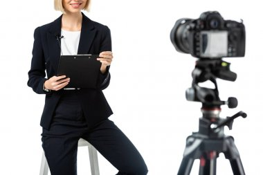 Cropped view of smiling anchorwoman with clipboard sitting near digital camera on blurred foreground isolated on white stock vector