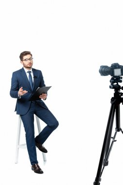 News commentator with clipboard sitting on high stool near digital camera on white, blurred foreground stock vector