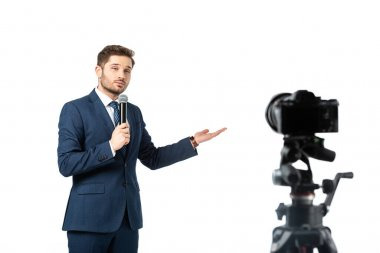 Journalist with microphone pointing with hand while looking at digital camera isolated on white, blurred foreground stock vector