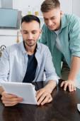fröhliches gleichgeschlechtliches Paar lächelt beim Blick auf digitales Tablet