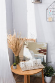 architectural maquette on table near spikelets and paintings at home studio