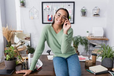 Happy african american architect adjusting eyeglasses while sitting on desk and smiling at camera stock vector